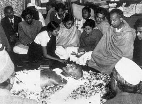 February 1948:  The niece of Mahatma Gandhi (Mohandas Karamchand Gandhi) places flower petals on his brow as he lies in state at Birla House, New Delhi, after his assassination. Immediately after this picture was taken the procession left for the burning ghat on the banks of the river Jumna, where the cremation took place.  (Photo by Keystone/Getty Images)