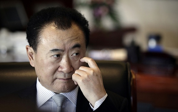 Wang Jianlin, chairman of Dalian Wanda Group, touches his face during an interview at his office in the company's headquarters in Beijing in this December 3, 2012 file photo. Chinese property developer Dalian Wanda Group says it can afford to spend as much as $5 billion every year to buy foreign firms or assets, underscoring the rising clout of the firm as it expands abroad. To match Interview CHINA-WANDA/    REUTERS/Suzie Wong/Files (CHINA - Tags: BUSINESS PROFILE HEADSHOT REAL ESTATE CONSTRUCTION)